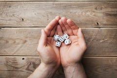Obsługuje mienia w ręk białych kostka do gry nad drewnianym stołowym odgórnym widokiem Uprawiać hazard przyrząda Gra szansy pojęc obraz stock