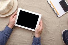 Obsługuje mienie pastylkę z pustego ekranu lying on the beach na plaży Obraz Stock