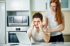 Obsługuje myśl z rękami na jego głowie i jego uśmiechniętej kobiecie używa laptop obrazy stock