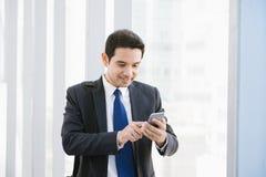 Obsługuje na mądrze telefonie - młody biznesmen w lotnisku Przypadkowy miastowy fachowy biznesowy mężczyzna używa smartphone zdjęcia stock