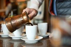 Obsługuje nalewać turecką, grecką kawę od garnka/ Zdjęcie Stock