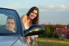 Obsługuje napędowego samochód, piękna kobieta przyglądająca za kabriolecie przy kamerą zdjęcie stock