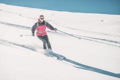 Obsługuje narciarstwo z piste na śnieżnym skłonie w włoskich Alps z jaskrawym słonecznym dniem zima sezon, Prochowy śnieg z narci zdjęcia royalty free