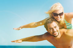 Obsługuje nieść jego żony na plaży w wakacje Fotografia Stock