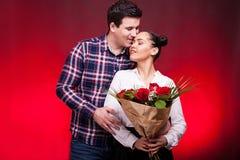 Obsługuje obejmować jej żony podczas gdy trzyma róża bukiet w rękach Zdjęcia Royalty Free