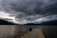 Obsługuje obsiadanie na krawędzi drewnianego doku na Harrison dopatrywaniu i jeziorze nadchodząca burza zdjęcie royalty free