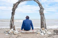 Obsługuje obsiadanie na plaży na kawałku driftwood fotografia royalty free