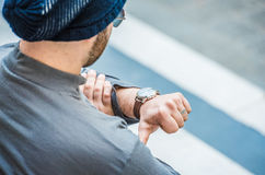 Obsługuje obsiadanie na schodkach i patrzeć jego zegarek - zamyka w górę widoku obrazy stock