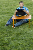 Obsługuje obsiadanie na trawie outside przed stołem Fotografia Royalty Free