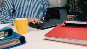Obsługuje obsiadanie przy biurkiem pracuje z laptopem od domu obraz stock