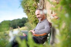Obsługuje obsiadanie w krześle ogród z pastylką w rękach Fotografia Royalty Free