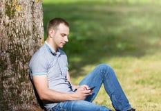 Obsługuje obsiadanie w parku i używać mądrze telefon Zdjęcie Royalty Free