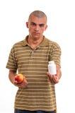 Obsługuje ofiary pigułkę w jeden jabłku w inny i ręce. Zdjęcie Royalty Free