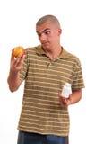 Obsługuje ofiary pigułkę w jeden jabłku w inny i ręce. Fotografia Stock