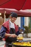 Obsługuje ono uśmiecha się, przygotowywać i słuzyć paella, typowy hiszpański posiłek Obraz Stock