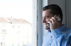 Obsługuje opowiadać na telefonie patrzeje przez okno w domu obraz royalty free