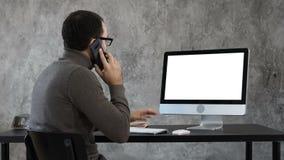 Obsługuje opowiadać na telefonie w biurowym i patrzeć na ekranie komputerowym Biały pokaz zbiory