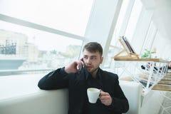 Obsługuje opowiadać na telefonie z filiżanką gorący napój w jego rękach Mężczyzna z brodą siedzi w sklep z kawą i je obiad Zdjęcie Stock