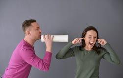 Obsługuje opowiadać przez tubki i kobiety czopuje jej ucho Obrazy Stock