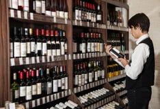 Obsługuje patrzeć butelkę wino w sklepie wino zakupy Fotografia Stock