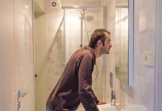 Obsługuje patrzeć go w lustrze w łazience Zdjęcia Royalty Free