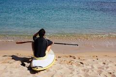 Obsługuje patrzeć horyzont podczas gdy siedzący na plaży Zdjęcie Stock