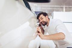 Obsługuje patrzeć nowego samochód w przedstawicielstwo handlowe salonie zdjęcia stock