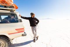 Obsługuje patrzeć słońce, SUV jedzie Salar De Uyuni pustynię zdjęcie royalty free
