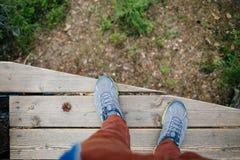 Obsługuje patrzeć w dół na liściach stoi na drewnianym moscie Zdjęcia Royalty Free