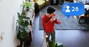 Obsługuje pić kawę podczas gdy texting na jego telefonie 4k zdjęcie wideo
