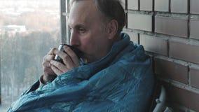 Obsługuje pić kawę w ranku w kuchni w domu Marznął i zawijał w koc zdjęcie wideo