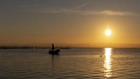 Obsługuje połów w łodzi przy zmierzchem w Albufera Walencja fotografia royalty free