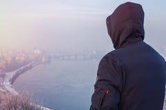 Obsługuje podróżnika patrzeje zimy miasta krajobraz w kapiszonie Obraz Royalty Free