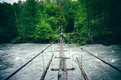 Obsługuje podróżnika wycieczkuje na drewnianym moscie nad rzeką Fotografia Stock