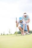 Obsługuje pomagać kobiety umieszcza piłkę na polu golfowym przeciw niebu Obraz Royalty Free
