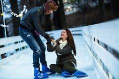 Obsługuje pomaga kobiety wzrastać up na łyżwiarskim lodowisku Fotografia Stock