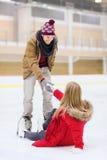 Obsługuje pomaga kobiety wzrastać up na łyżwiarskim lodowisku Obrazy Royalty Free