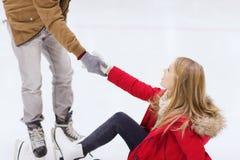 Obsługuje pomaga kobiety wzrastać up na łyżwiarskim lodowisku Obrazy Stock