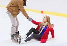 Obsługuje pomaga kobiety wzrastać up na łyżwiarskim lodowisku Fotografia Royalty Free