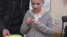 Obsługuje pomaga małej dziewczynki z kwiatem na kierowniczym dzianiu szydełkowym festiwale tworzenie _ zbiory wideo
