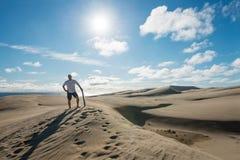 Obsługuje pozować z deską przy Te Paka piaska diunami obrazy stock