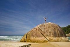 Obsługuje pozycję na dużym kamieniu w tropikalnej plaży z górami Fotografia Stock