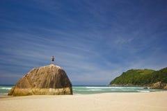 Obsługuje pozycję na dużym kamieniu w tropikalnej plaży z górami Obraz Royalty Free