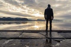 Obsługuje pozycję przy brzeg, patrzeje spokojnego morze Odbicia mężczyzna w lodzie na ziemi Mgła i mgła zdjęcie stock