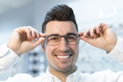 Obsługuje próbować na szkłach w okulistycznym sklepie podczas gdy ono uśmiecha się szczęśliwy obraz royalty free
