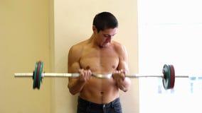 Obsługuje pracować jego ręki przy gym, On podnosi działanie i dumbbells jego bicepsy zdjęcie wideo