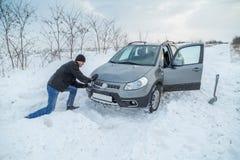Obsługuje przeszuflowywać śnieg uwalniać jego zablokowanego samochód Obraz Stock