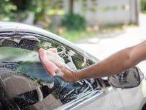 Obsługuje rękę trzyma gąbkę naciera samochód z pianą Carwash przeciw obraz stock