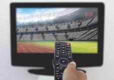 Obsługuje rękę używać pilot do tv podczas gdy oglądający tv Obrazy Stock