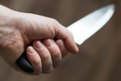 Obsługuje rękę z kuchennym nożem Zdjęcie Stock